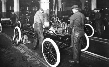 Two workers put the engine in a Ford T